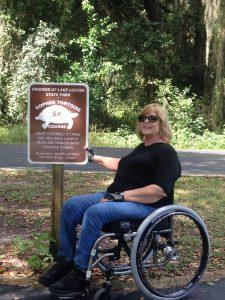 Photo of Joyce Tucker in wheelchair at park entrance